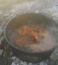 A dutch oven meal made up of chicken and potatoes